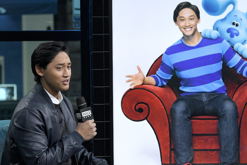 """""""Blue's Clues & You!"""" host Joshua Dela Cruz. In one image he is sitting down holding a microphone. In another image he is sitting in his red thinking chair smiling, next to the dog Blue."""